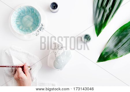 painted ceramic cup on white background top view whith hands