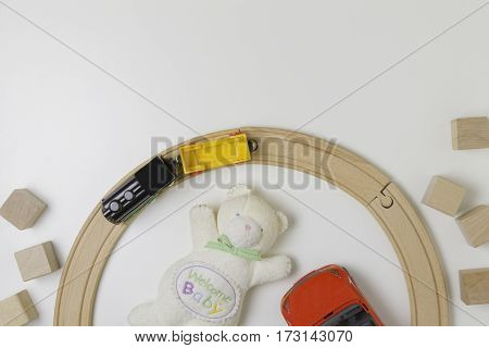 Toys frame with teddy bear, wooden cubes , red car and toy train on the white background. Top view