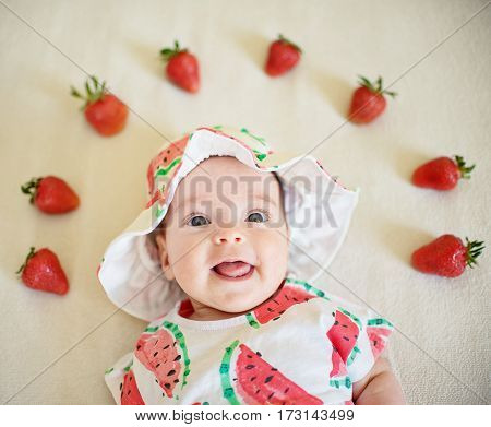 A cute baby girl dressed in a hat and a dress with water melon print on the strawberry background