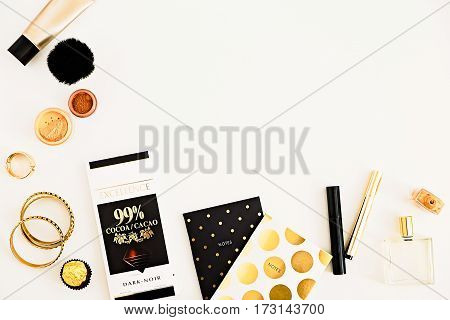 Beauty products accessories polka dot notepads dark chocolate top view. Makeup still life. Gold black and white glamour style