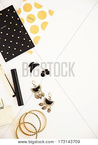 Black and gold on white. Woman's makeup and accessories polka dot note pad. Beauty blog flat lay. Negative space