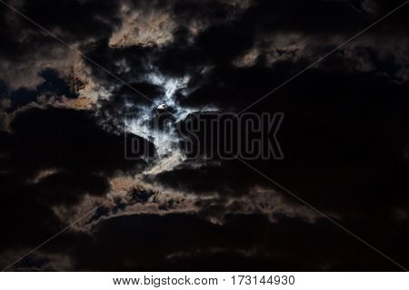 The night is dark gloomy sky. The moon shines through the dark clouds. Full moon.  Dark gothic background. Dark night