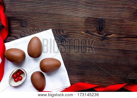 Easter chocolate eggs top view on wooden background mock up.