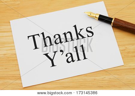 Southern thank you message A white card on a desk with a pen with text Thanks Y'all