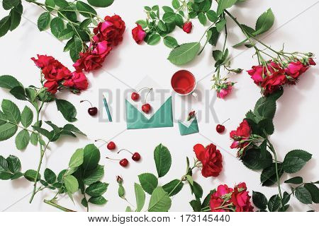 Graphite pencil concept with red rose tea ripe cherries small envelopes with green leaves rose lay on white background. Tea drinking during work. Healing drink concept. Berry compote. Morning designer. Flat lay. Art concept