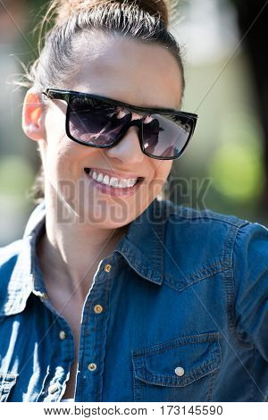 Beautiful fashionable young woman with brown hair and sunglasses posing in the park