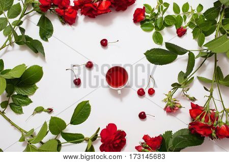 Red karkade tea in a white mug ripe cherries frame of roses with green leaves on a white background. Tea on white texture Juice from the berries. A refreshing drink. Flat lay art copyspace top view tea.