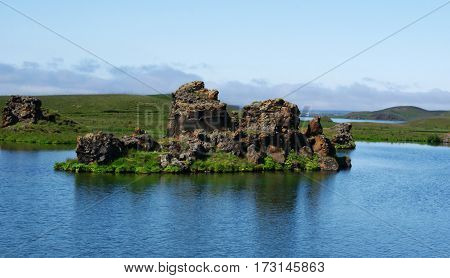 the Myvatn lake in north of Iceland with a little rocky-island in the middle around the lake green fields and single rocks