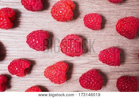 Red ripe raspberry lie on a wooden background. Copyspace flat lay top view. Macro