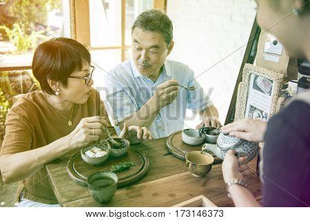 Waitress pouring tea for senior adult couple