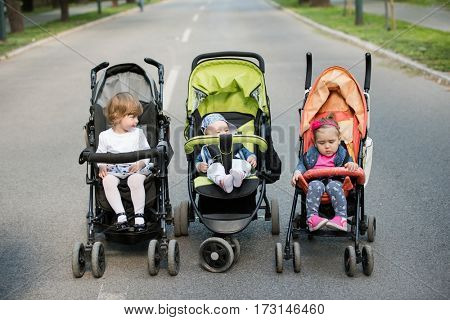 beautiful babies sitting in a stroller in the park