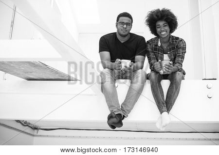 Happy young African American couple having break during moving to new house