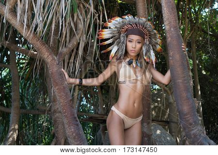 Sensual Native American Indian looking woman wearing nude bikini and indian feather hat looking into the camera while standing between tropical tress on sunny summer day
