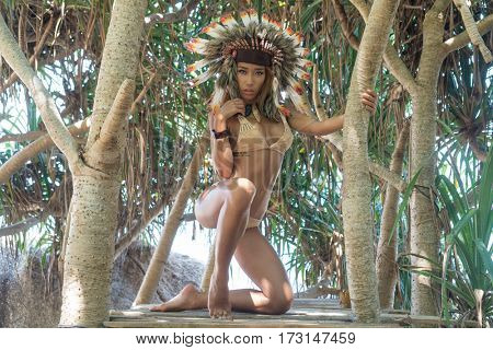 Sensual Native American Indian looking woman wearing nude bikini and indian feather hat looking into the camera and posing between tropical tress on sunny summer day