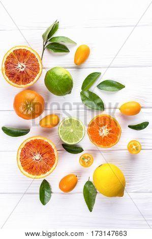 Fresh citrus fruits with leaves. Sicilian oranges, lemon, mandarin, lime, kumquat on white wooden background