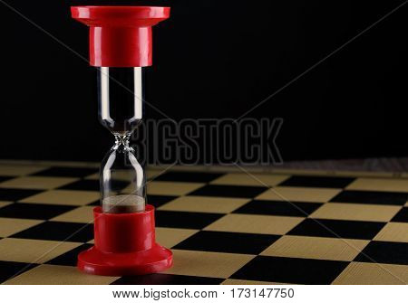 red hourglass on an empty chess board as the End of Game concept, shallow DOF with selective focus