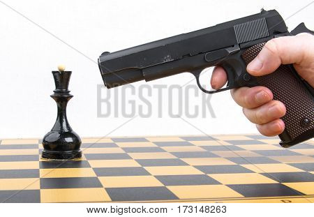 male hand with gun took aim at chess piece