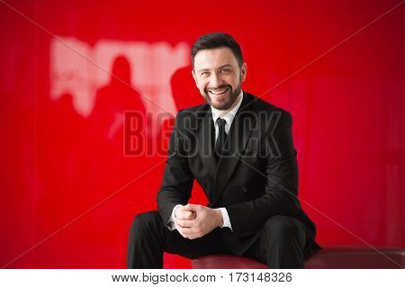 man in black suit on red background