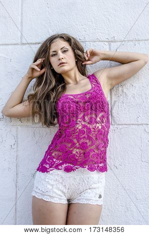 Beautiful young woman in a transparent pink top walks through the city streets