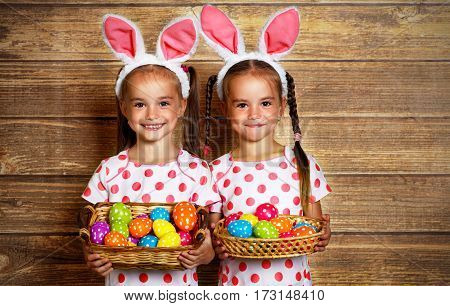 Happy easter! cute twins girls sisters dressed as rabbits with eggs on wooden background