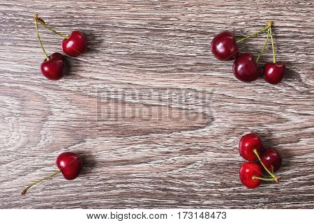 Red ripe juicy sweet cherry lies on vintage wooden background. Sweet summer berries. Flat lay cherry top view. Copyspace healthy food. Summer cherry