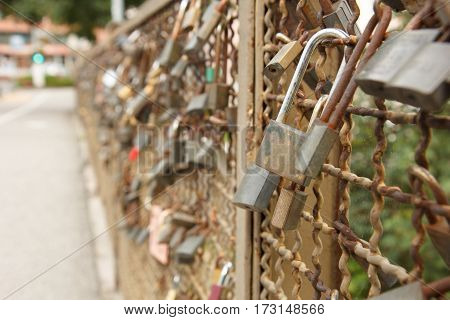 Love locks locked on the fence of the bridge in Bruneck Italy