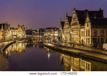 GHENT BELGIUM - 18TH FEB 2016: A view of beautiful old buildings along Korenlei Graslei and the River Leie in Ghent Old Town at night. Reflections can be seen in the water.
