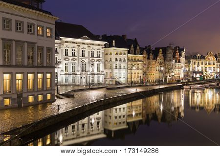 GHENT BELGIUM - 18TH FEB 2016: A view of beautiful old buildings along Korenlei and the River Leie in Ghent Old Town at night. Reflections can be seen in the water.