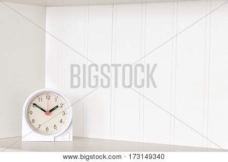 Horizontal shot of a clock on an empty white shelf with copy space.
