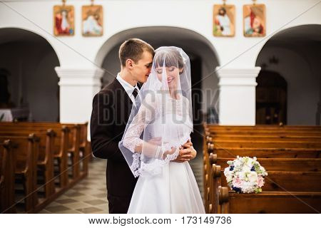 New happy family. Groom and bride in a white  wedding dress in the church. Wedding ceremony. Happy family. Creating a new family