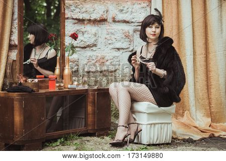 retro girl sitting at a dressing table and holding a necklace in hands