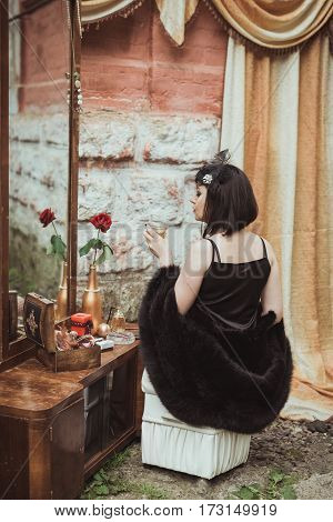 retro girl sitting at a dressing table and holding a glass of alcohol in hand