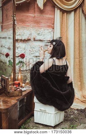 retro girl sitting at a dressing table and drinking alcohol from a glass