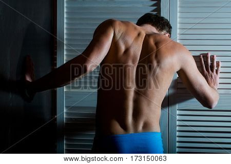 young handsome macho man in blue pants with muscular body and sexy naked back at white wardrobe door