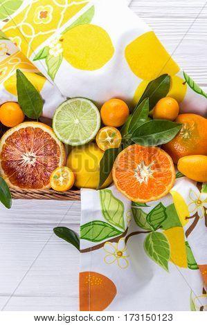 Fresh citrus fruits with leaves. Orange, lemon, mandarin, lime, kumquat on white wooden background