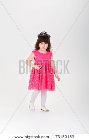 beautiful little brunette girl in pink Princess dress with a crown on a gray background. cute baby