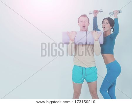 happy couple of pretty woman or cute girl with fitness mat and handsome guy man with muscular torso and sexy body training in sport gym with dumbbells isolated on white background copy space