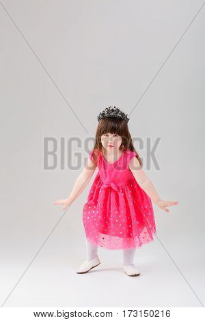 beautiful little brunette girl in pink Princess dress with a crown trying to curtsy on a gray background. cute baby