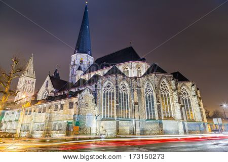 GHENT BELGIUM - 18TH FEBRUARY 2016: The outside of St. James' Church Antwerp (Sint-Jacobskerk) in Ghent at Night. The trails of traffic can be seen going round a roundabout nearby.