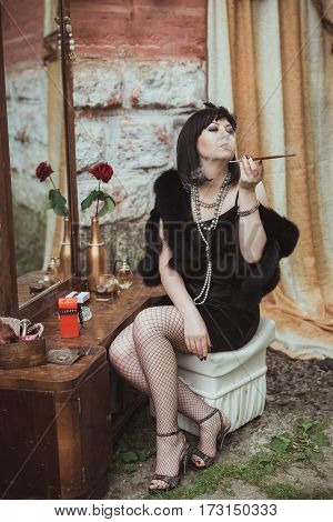 retro girl sitting at a dressing table and smoking cigarette with mouthpiece