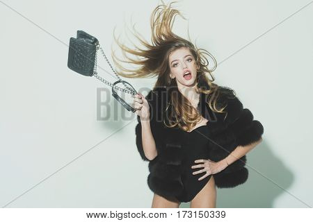 young pretty woman or cute sexy girl with long beautiful curly blonde hair and adorable surprised face in black fur vest or waistcoat holds fashionable bag with chain on white background