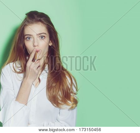 young pretty woman or cute sexy girl with long beautiful blonde hair and adorable surprised face smoking cigarette in white shirt on green background copy space