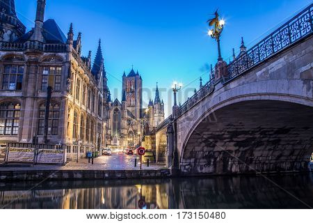 GHENT BELGIUM - 19TH FEB 2016: A view towards Saint Nicholas' Church in Ghent City Center at dusk in the morning. Reflections can be seen in the river Leie