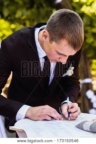 Groom and bride in white dress on background of the arch. Wedding ceremony. Happy family. The man puts his signature. Putting signature during registration
