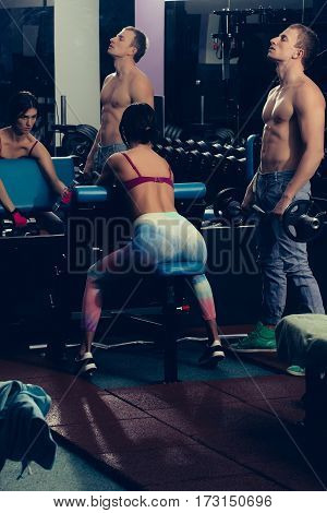 Muscular Man And Girl At Gym With Dumbbells And Barbell