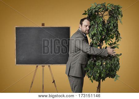 Businessman hugging a tree at office - studio shot