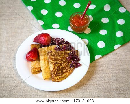 Beautiful baked pancakes with red berries on a white plate. On the table green with white polka dots linen towel and a jar of red caviar.