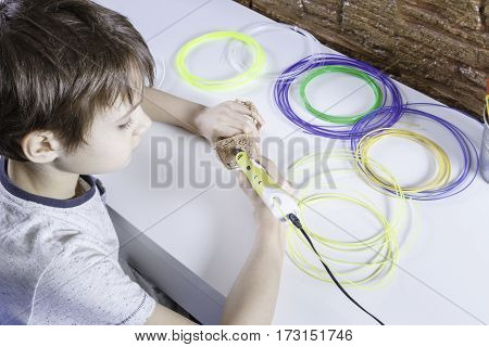 Happy child creating with 3D printing pen. Kid making new item. Creative technology leisure education concept