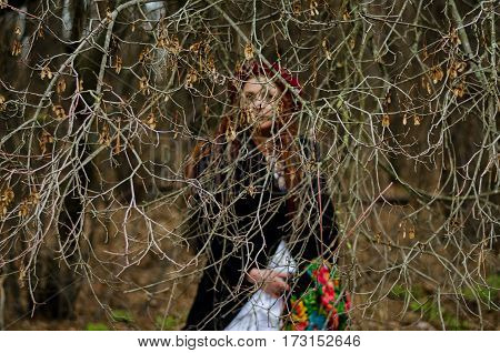 Beautiful boho-style girl with dreadlocks in a white wedding dress on background of thin bare autumn twigs selective focus and faded colors