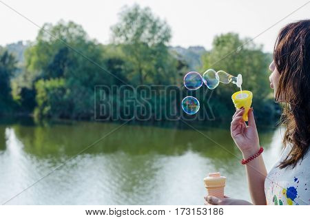 Portrait of a summer girl blowing soap bubbles faded colors and green natural background